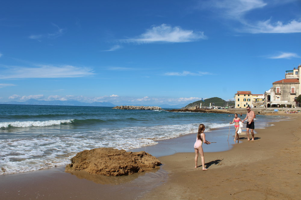 A family playing and swimming in the pristine sea at Santa Maria Castellabate in October.