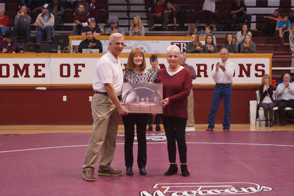 """David C. Matthews -  Dave's daughters, Fran Little and Jeanie Vance were at the dual to receive the honor in memory of their Dad.  David C. Matthews was a three-time All American and 1938 National Champion wrestler from the University of Oklahoma. In 1945, David was a young attorney looking to raise his growing family in a small town that was a county seat. Fortunately, for Perry, he moved here. David, or Dave as he was called around town, had a powerful and long lasting impact on the Perry wrestlers. His incredible support helped lay the foundation for the championship teams of the 50s and 60s which continues today under the motto """"Wrestling Lives Here!"""" Former wrestlers shared that Dave was a role model and he was always present when needed. He treated every kid, no matter the ability level, like he was a champion. One former wrestler recalls Dave's special touch in inspiring young men to be the best they could be.  Dave's support went far beyond the wrestling mat. He often times provided financial assistance and legal guidance to those in need. In fact, one former wrestler affectionately referred to him as the """"godfather of the youth in Perry."""" He sometimes even became a legal guardian to help resolve a family challenge. One perfect example was Dave becoming the legal guardian of recent Wrestling Hall of Fame inductee, the late Tony Macias. His support, encouragement and positive influence helped lead a countless number of wrestlers to successful careers once they graduated from high school. Dave's daughters, Fran Little and Jeanie Vance were at the dual to receive the honor in memory of their Dad."""