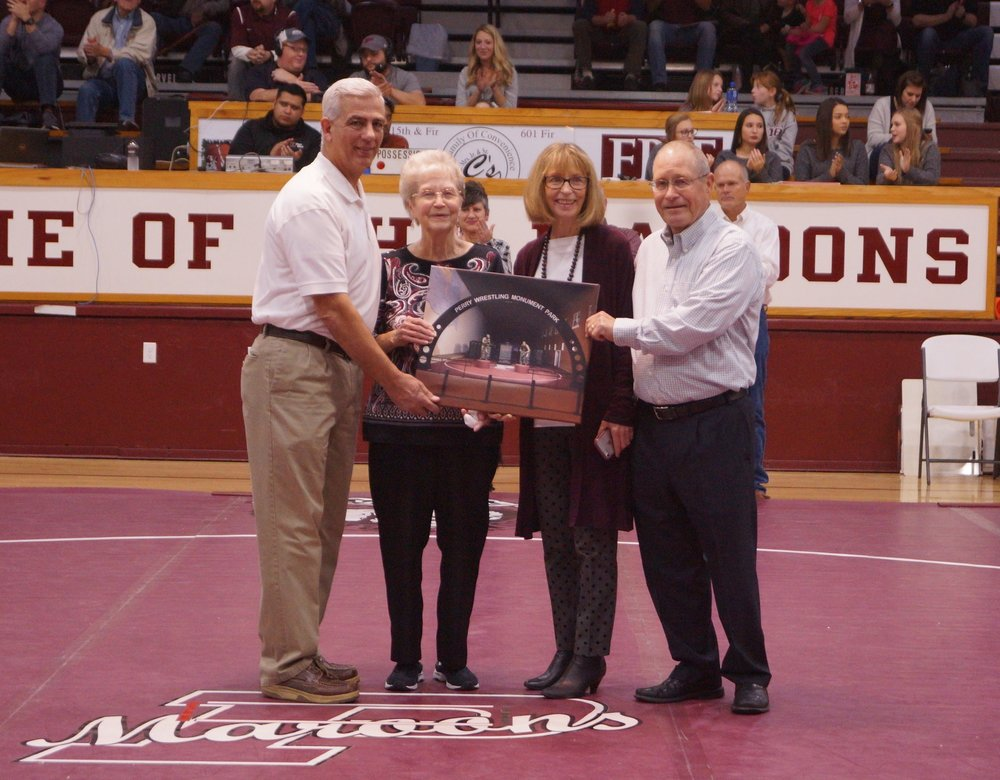 """Irl W. Henry -  Representing Irl at the presentation was his family, Hulda Henry Trumbla, Kathy Henry and Terry Henry.  Irl wrestled for the Maroons and was selected as a Captain of the 1940 team. For many years he gave of his time as the announcer and """"The Voice of Perry Wrestling."""" He worked all the duals and countless tournaments. When he worked tournaments he would get paid a small stipend. He always donated this back to the wrestling program and never kept it for himself. He was recognized as the Perry Wrestling Fan of the Year in 1989 and 1996. In 2004, he was recognized during the state finals for attending the State Wrestling Tournament for 54 consecutive years! But, the thing that made Irl special is that he took the time to get to know each individual wrestler. He was always there with an encouraging word or a pat on the back. Even though he passed away several years ago, he left a lasting impression on many young men. His obituary even stated, """"He is now with the Lord in heaven and will continue to cheer for the PHS wrestlers from the bleachers in the sky."""" Representing Irl at the presentation was his family, Hulda Henry Trumbla, Kathy Henry and Terry Henry."""