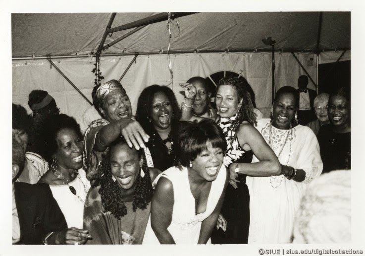 Left-to-right, front: Mari Evans, Susan Taylor, Oprah Winfrey. On the back row: Maya Angelou, Joan Sandler, Angela Davis, Eleanor Traylor, Amina Baraka. Howard Dodson appears behind Sandler and Davis. The women were laughing at Toni Morrison who was dancing one the occasion of her Nobel Party hosted by Angelou, 1994. Redmond photographed the event. courtesy Eugene B. Redmond and  SIUE/EBR African American Cultural Life .
