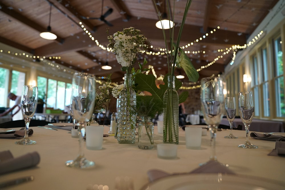 I used upwards of 8 different bottle shapes to create a eclectic yet cohesive centerpiece. We wanted people to be able to see each other over the flowers, as all the tables were round.