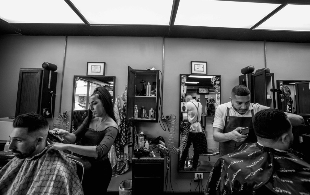 """His shop is a platinum trombone to his community. Born and raised in the Latino-Chicago village, he began cutting hair during his teenage years, and that's when everyone started knowing his name. """"Growing up in a lower income family. I couldn't afford to get a haircut, so I learned how to cut my own hair. Then my friends wanted me to cut their hair and I realized, I was a barber. My first goal was to become a licensed barber. I'm platinum now."""""""