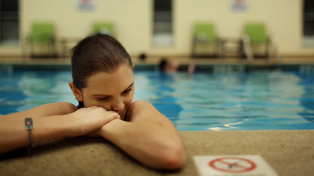 Best and Most Beautiful Things still: young woman in pool looks pensive.
