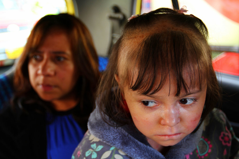 In a taxi- foreground, a young child with a skin condition, Maria. In the background her mother with a serious expression