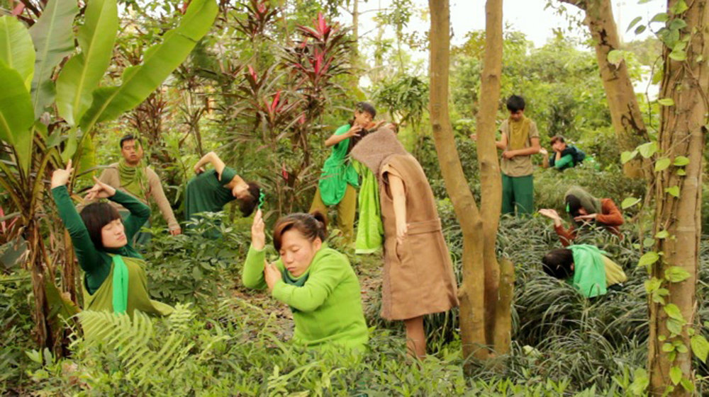 A large group of young Vietnamese people with varying disabilities perform an interpretive dance in the jungle. Their garb matches the surroundings.