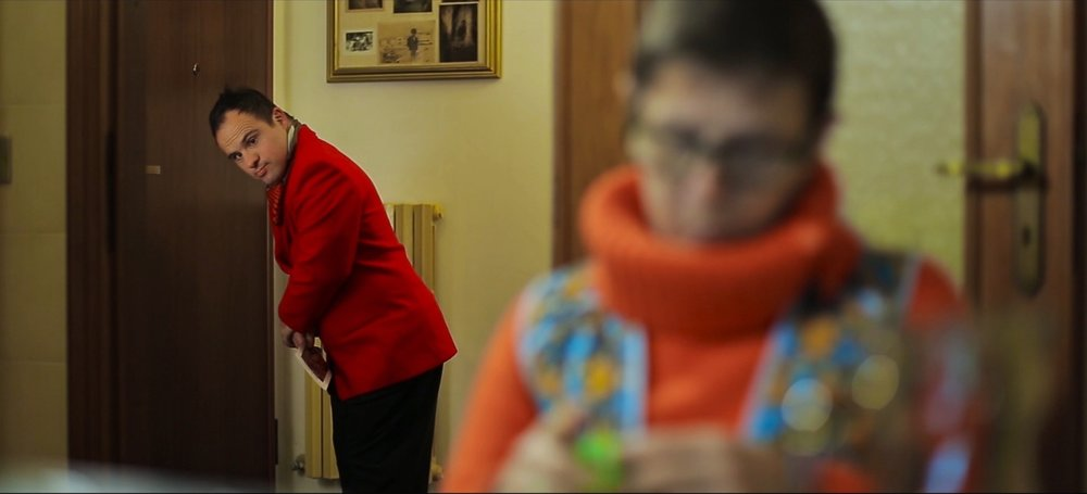 In a home. Foreground, blurry, older woman knitting. Background young white man with down syndrome, well dressed in a red coat, sneaks out of the house.