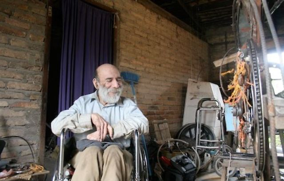 An older man who is bald with a white beard is sitting in a manual wheelchair with machine parts all around him.