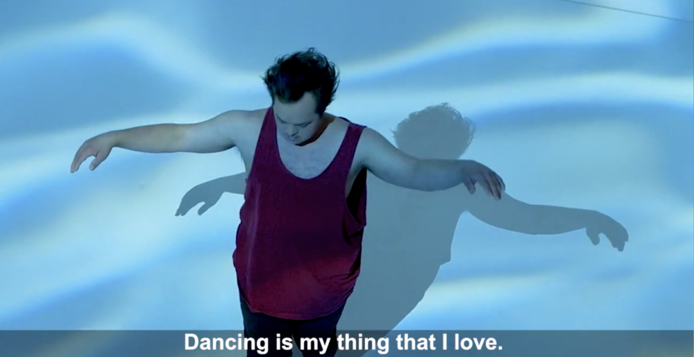 "A boy dances in front of lights which mimic water, and below, subtitle: ""Dancing is my thing that I love."""