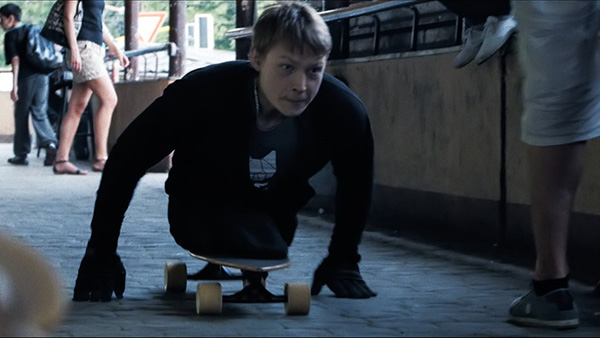 A young man rolls with his torso on a skateboard and pushes himself along a cobblestoned street.