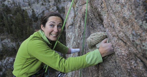 Maureen Beck, one armed rock climber smiles for camera as she is climbing up a cliff