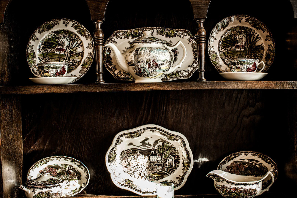 China tableware displayed in an antique wooden China cabinet.