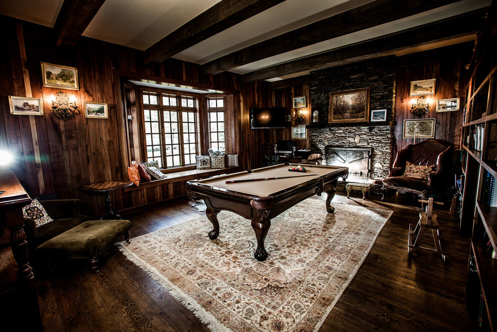 A typical English study room with a large bookcase on one wall facing an antique pool table.