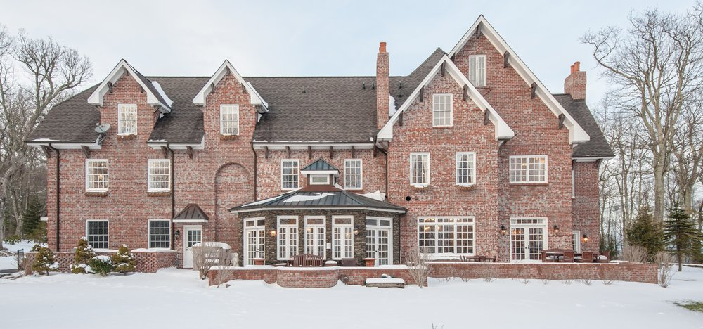 The back of Twickenham House in the winter. Snow covers the lawn and is sprinkled atop the roof of the house.