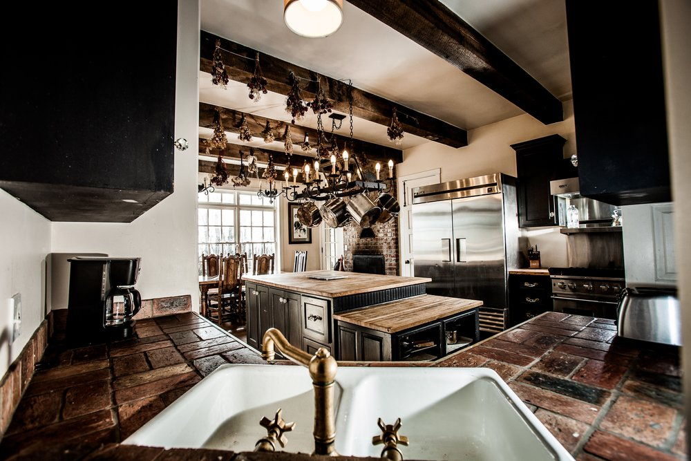 A farm style kitchen sink surrounded by warm, aged tile.