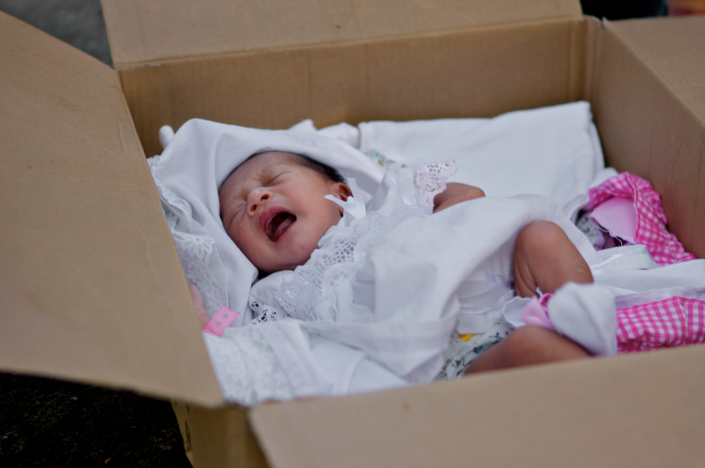 Newborn Karla in her box crib on the streets of Managua