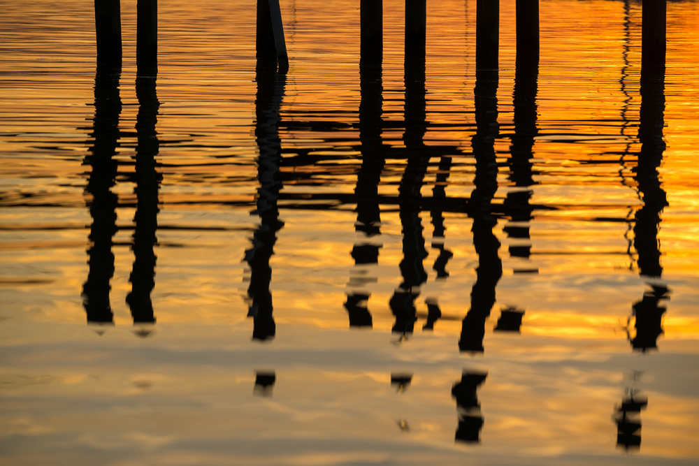 Reflections of the pier dock at sunset.