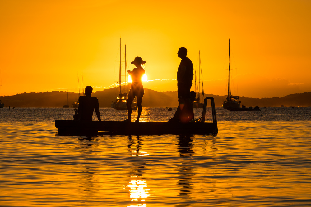 Silhouette of friends playing on a dock at sunset.