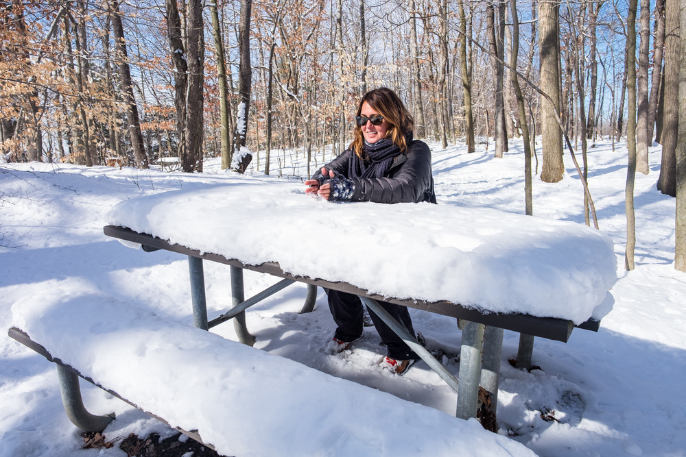 Stef waits for lunch to be served on her snowy picnic table.