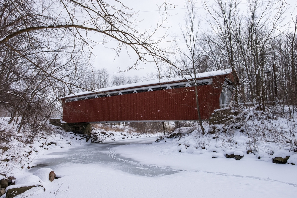 The Everett Covered Bridge and animal tracks crossing Furnace Run during a snowfall in winter, 2016.