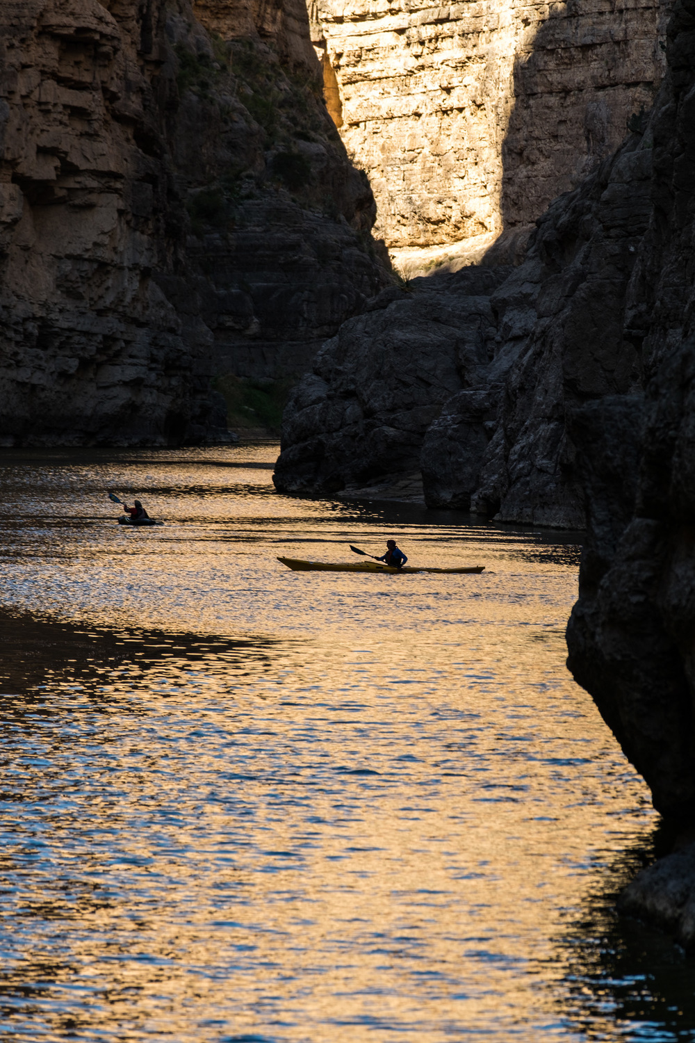 Kayakers in the distant canyon.