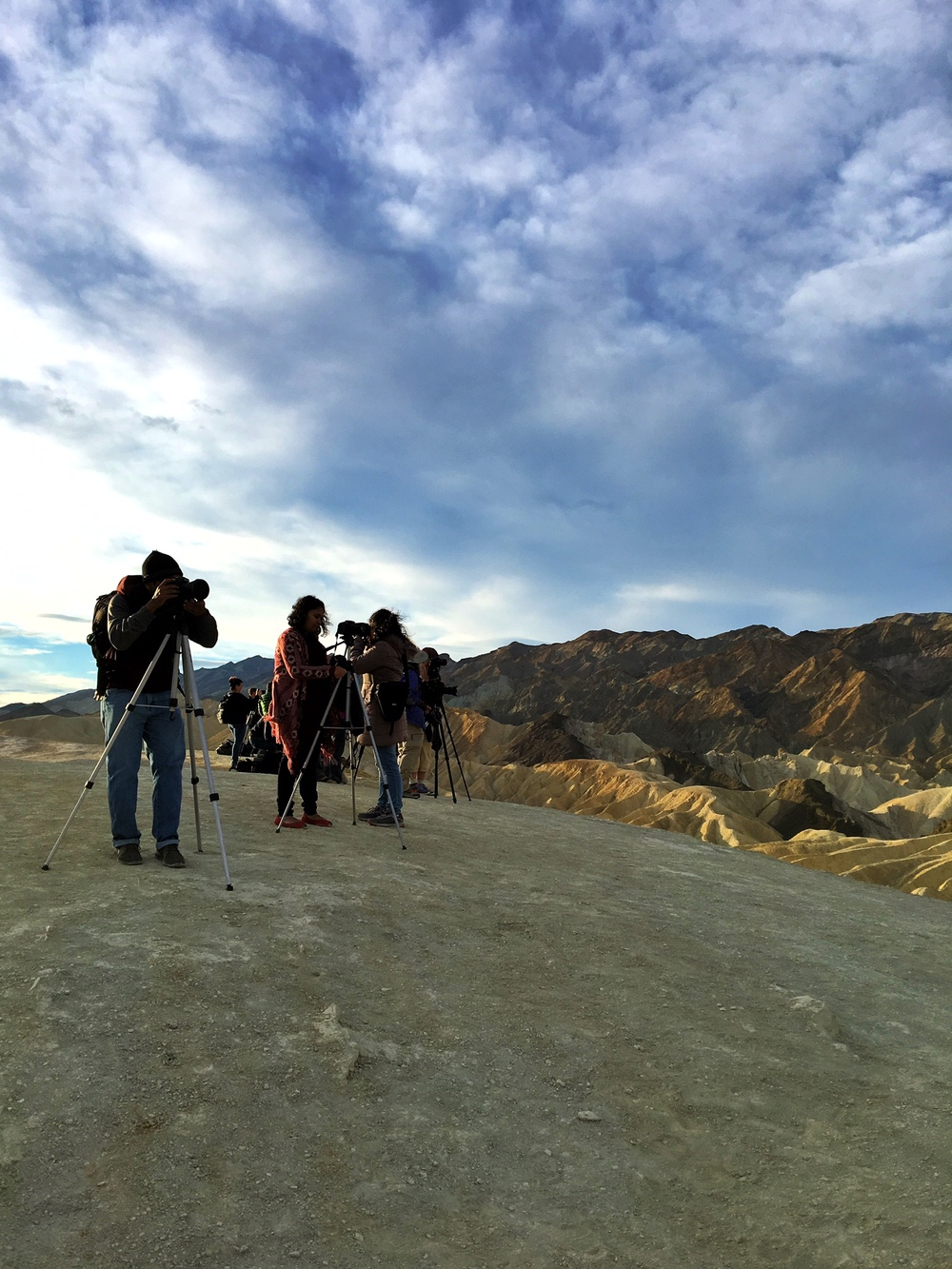 Sunrise photographers belly up at Zabriskie Point in Death Valley, one of the most popular sunrise spots in the park.