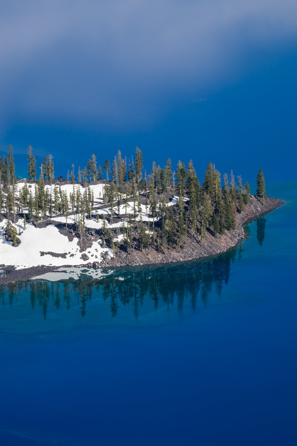 A small section of Wizard Island reflects in the crystal blue lake.