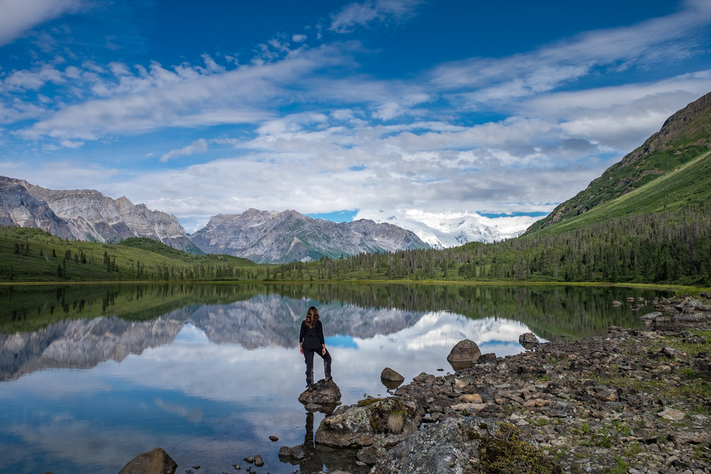 Stefanie takes in the early morning mountain air at an alpine lake where we camped for a night on our glacier/tundra backpacking adventure.