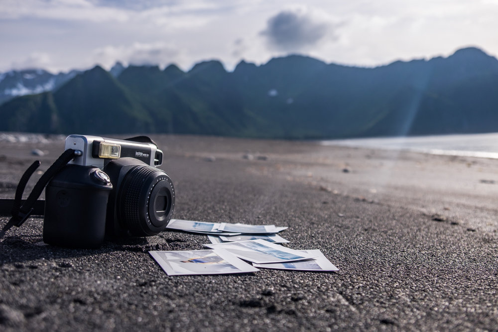 Instaxing on a black sand beach at Kenai Fjords National Park in Alaska.