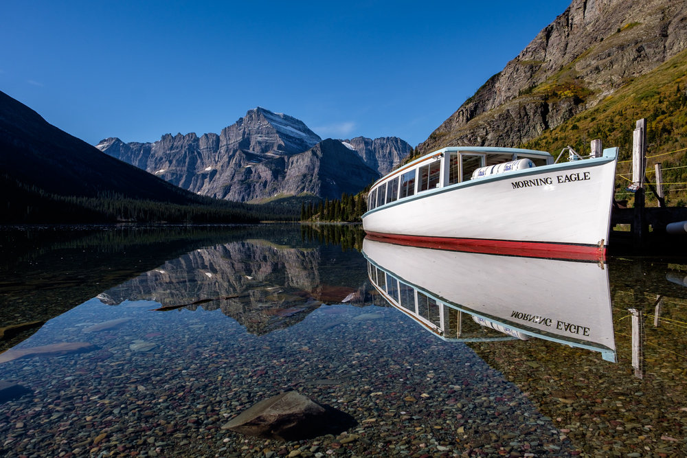 "A classic wooden boat used for guests tours, the ""Morning Eagle,"" enjoys a moment of rest on the perfectly clear Josephine Lake. Look at the color of those rocks!"