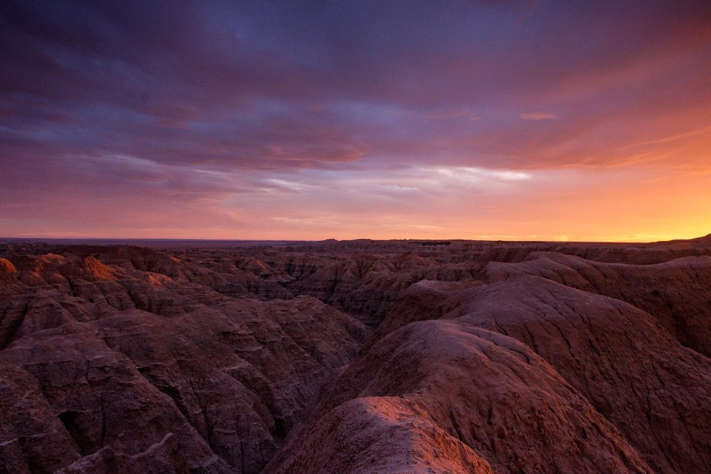 An October sunset warms the badlands landscape near the Pinnacles entrance of the park along Sage Creek Rim Road.