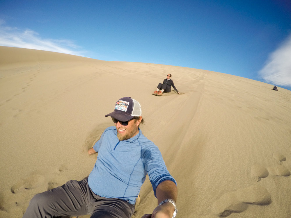 Flying down the dunes on our rented sand-boards!