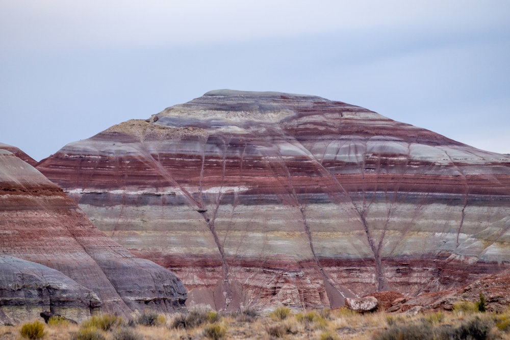 The Painted Desert on the Cathedral Road (also known as the Cainville Wash) appears as softly-contoured, banded hills in varying hues of brown, red, purple, gray, and green. The hills are composed of the Brushy Basin shale member of the Morrison Formation.