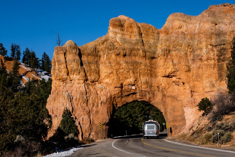 Wally the Airstream makes way through a natural arch in the Dixie National Forest en route to the park.
