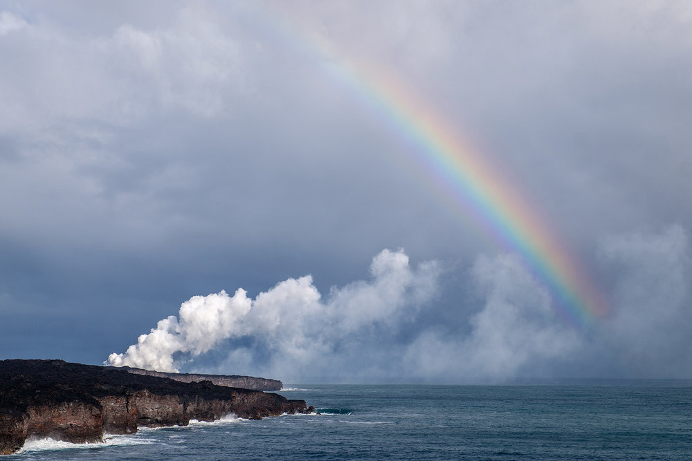 A steam cloud rises from where lava from Kīlauea meets the Pacific Ocean...