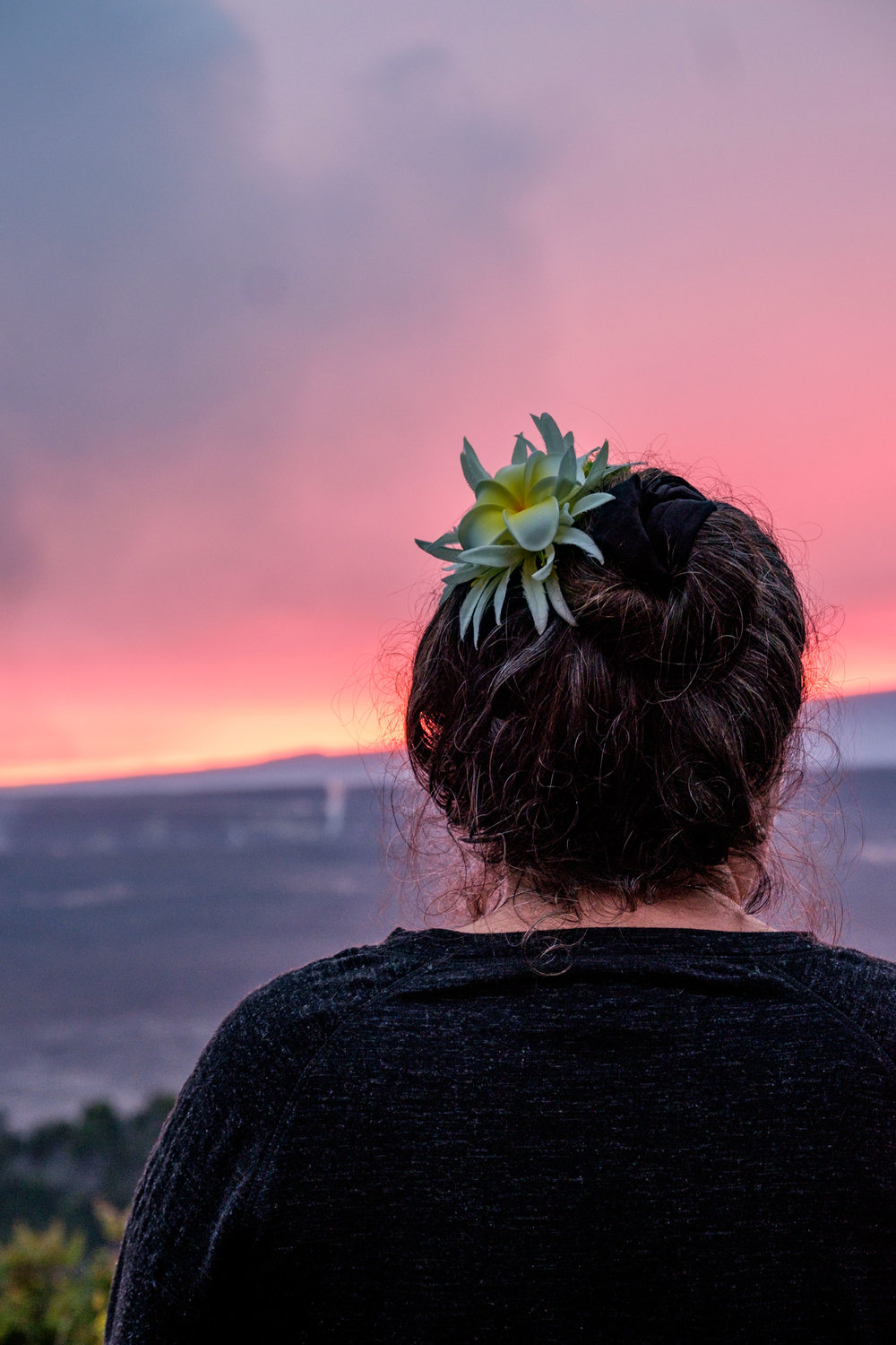 A woman with a plumeria watches an incredible pink sunset.