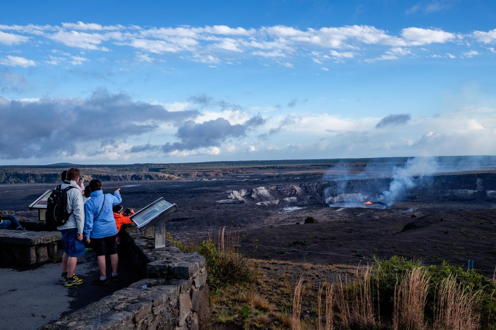 Hawai'i Volcanoes National Park visitors watch the wonder of the Halema'uma'u Crater erupting 100 feet away.