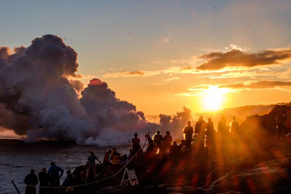 Locals, travelers, and photographers gather to watch Pele's creation meet the mighty sea.