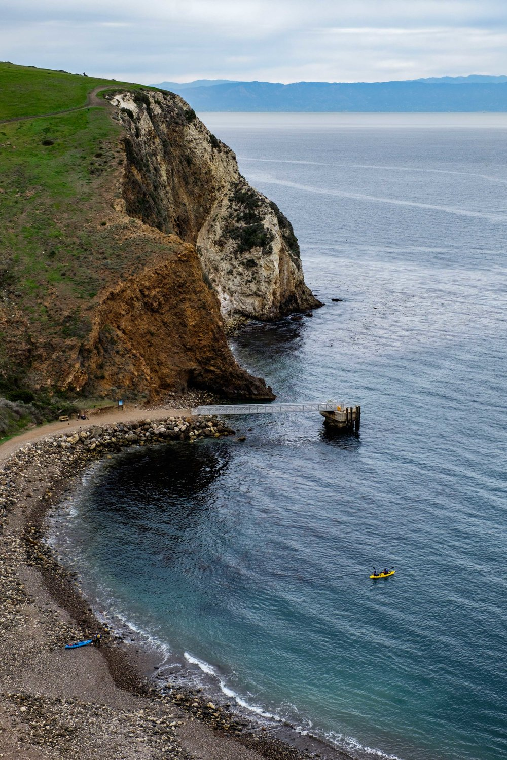 Looking down onto Smugglers Cove on Santa Cruz Island as kayakers push off into the marine sanctuary.