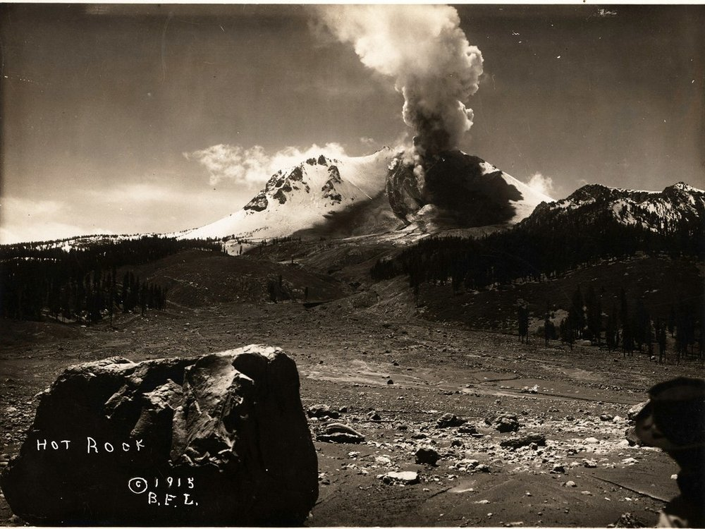 Steam rising from Lassen Peak after the devastating1915 eruption and a smoldering rock in the foreground. Credit: B.F. Loomis/NPS/Library of Congress