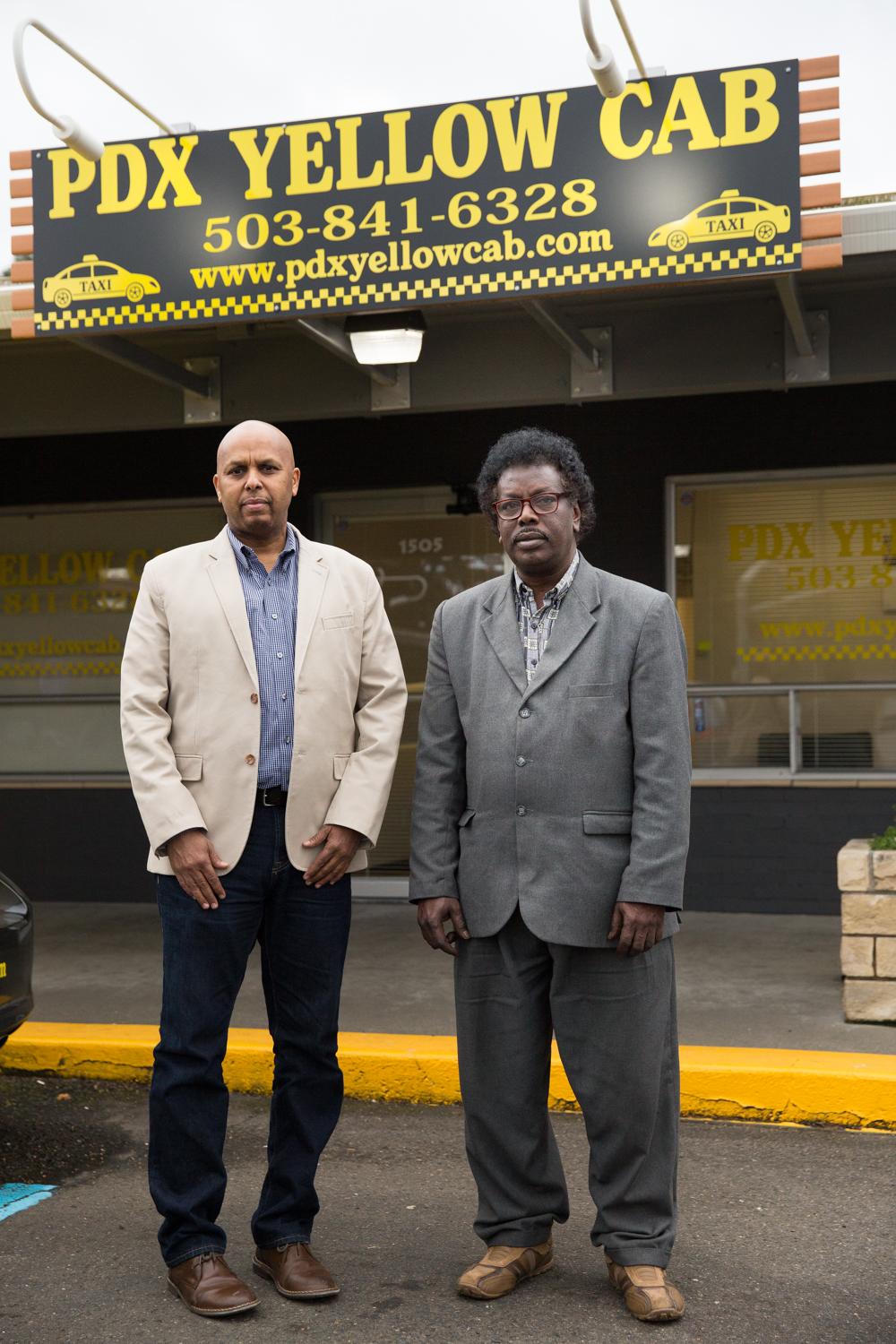 Dawood Ghedi, Operations Manager at PDX Yellow Cab, and Musse Olol of the Somali American Council of Oregon stand outside the company's East Portland location.