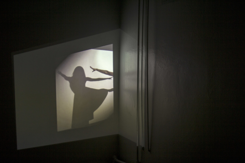 Across an expanse, Sarah O Donnell's piece pitches across two rooms. In the first, a cord connects a mirrored projection of a dancer to a hidden sound in the next room. As the mirror spins at the end of a line, it throws the projected dancer's image around the room. She flashes over the walls; the sound laments across the hall. Even when the sound's source is found inside a suspended bucket held by a line of rope, it remains elusive, mournful. Here, all that is torn asunder is brought not into union, but into proximity, just touching.