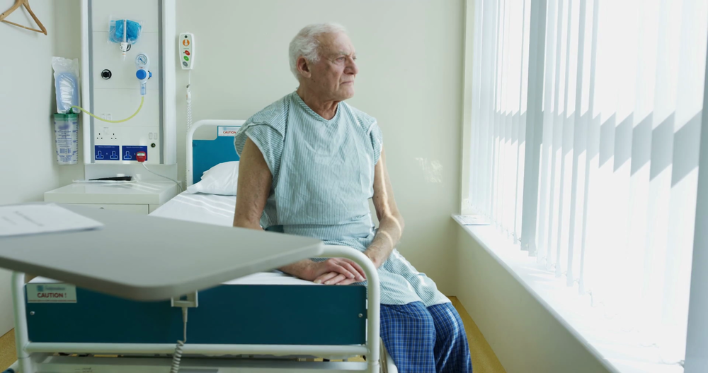 4k-portrait-of-smiling-elderly-patient-sitting-on-his-bed-in-hospital-room_bfgpzq7ftx_thumbnail-full01.png