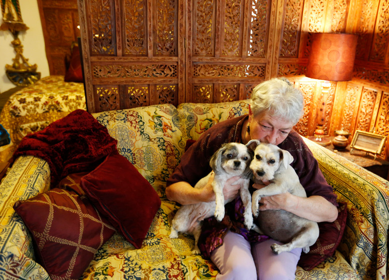 Bette Cyr gives attention to her dogs Sissy and Cassie at her home in Crawford, Colo. Cyr adopted her dogs from Debbie Faulkner,owner of the Black Canyon Animal Sanctuary and founder of the Silver Whiskers program