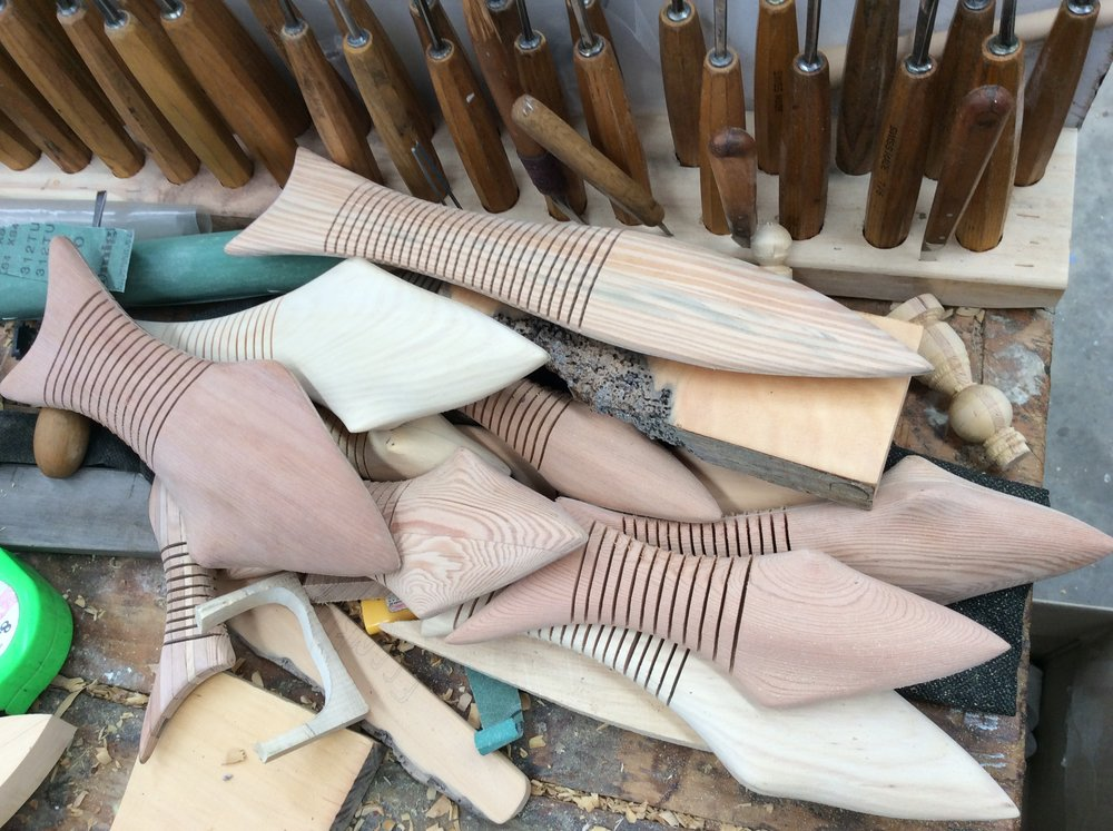 A pile of wooden fish under construction on Francis' bench.