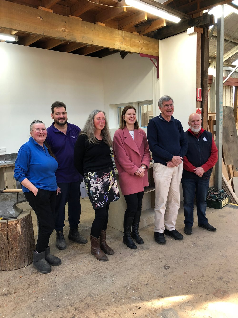 Christina Kent, Francis Shepherd, Anne Holst, Julie Collins, Alan Cato and Graham Rankin in front of the metal work area that is having a facelift.