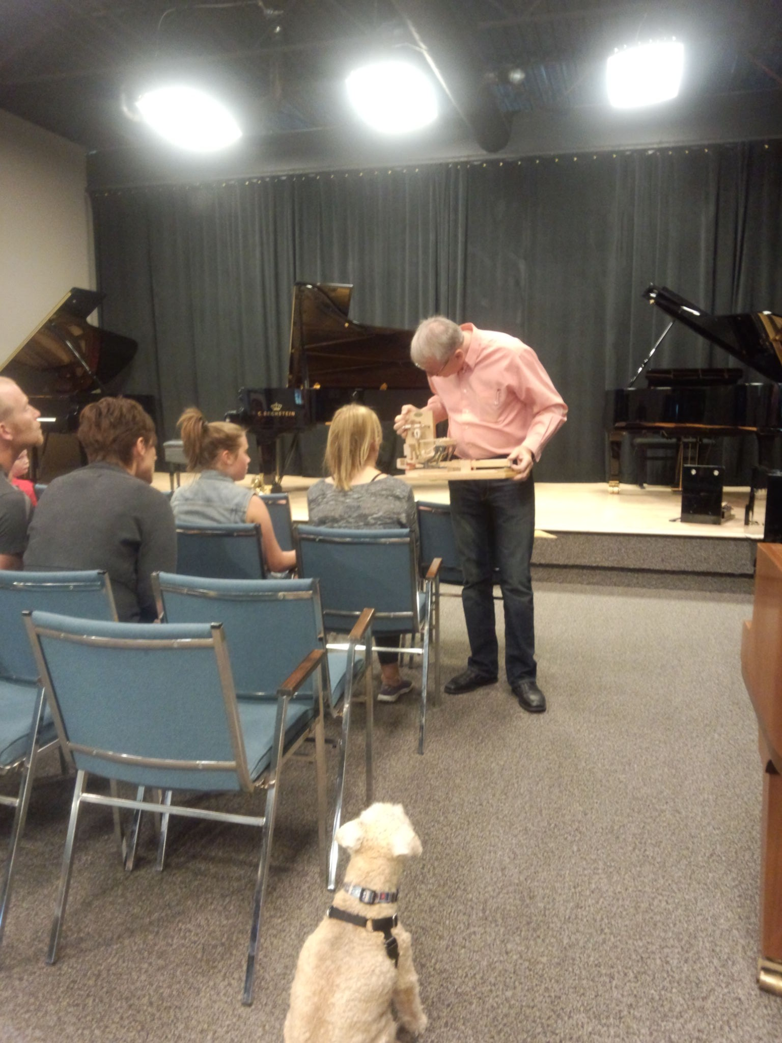 Maestro watches Registered Piano Technician Michael Lipnicki with showing off piano parts. Photo by R-M Arca.