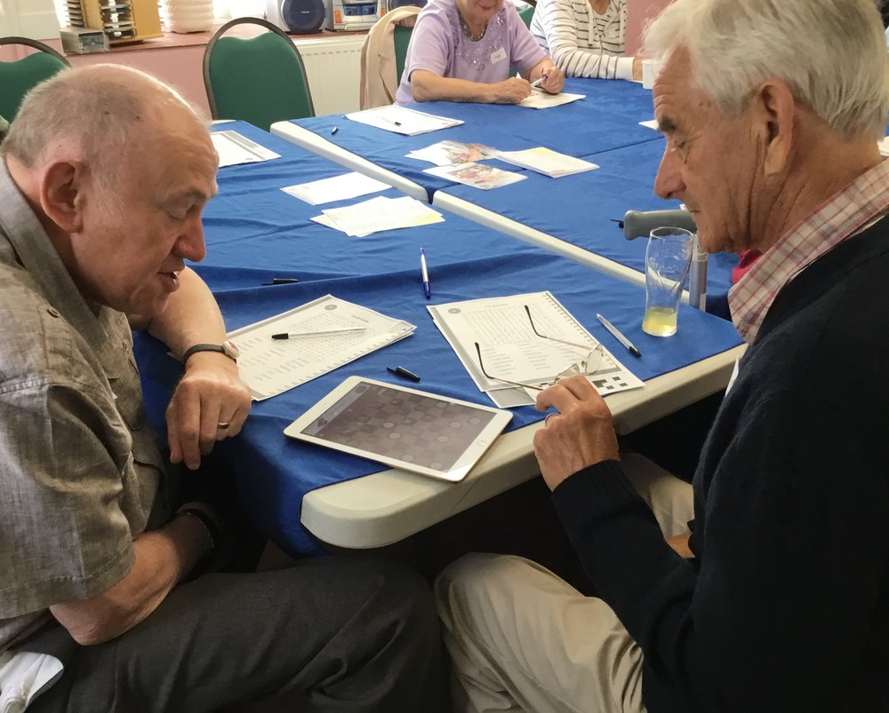 Two group members at the Alice Cross Centre Memory Café playing an AcTo Dementia recommended game of Draughts on the iPad