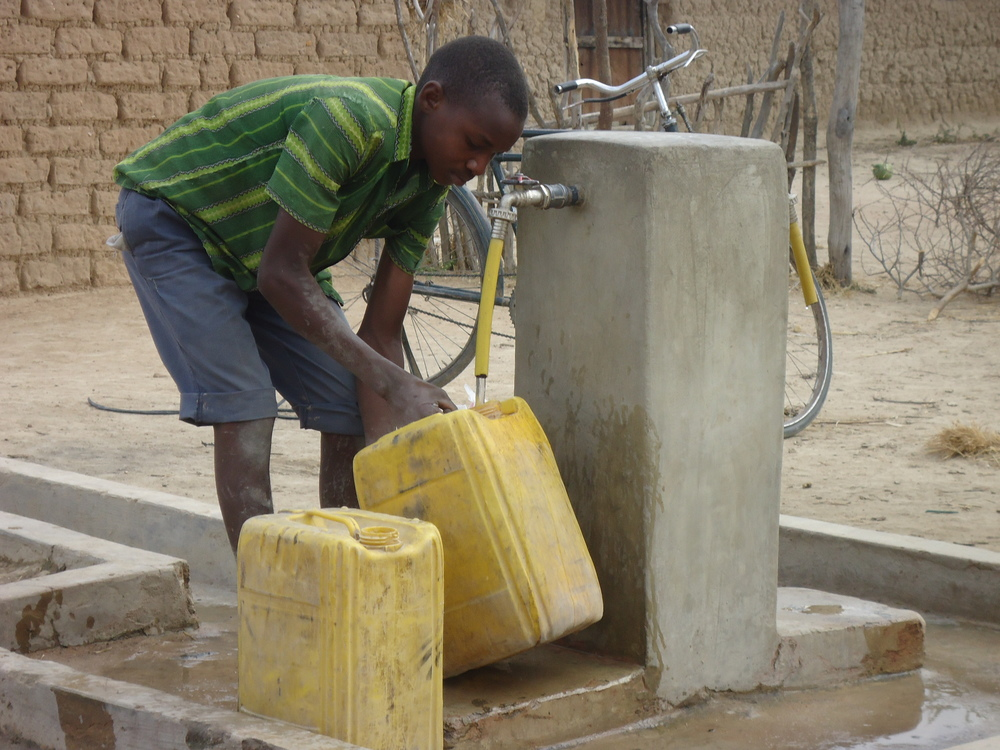 Boy collects water from  DP in Ihumwa village.JPG
