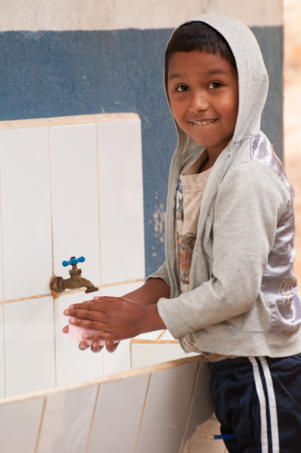 Child using water tap at school, Water for People