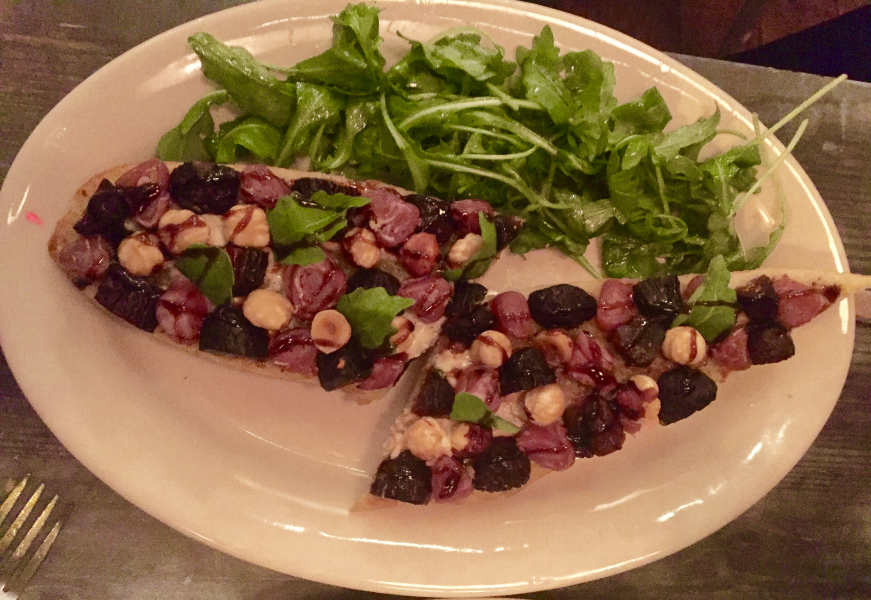 Tartine with figs, hazelnuts, prosciutto, raclette, and arugula salad.